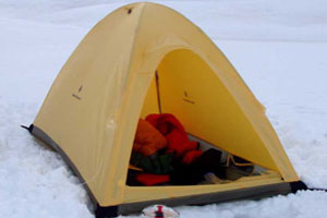 Light yellow single wall tent pitched in snow
