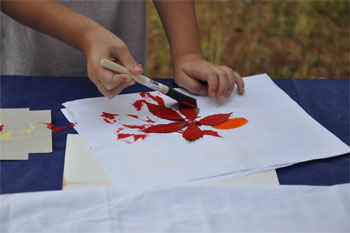 Child painting over a leaf making their camping scrapbook