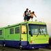 College kids standing on the roof of a green RV