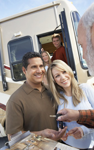 Salesperson handing over keys to the new owners of a class A motorhome