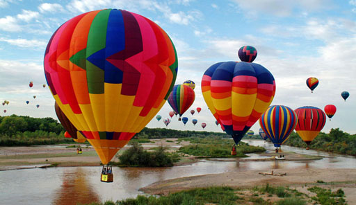 Lots of hot air balloons above a river