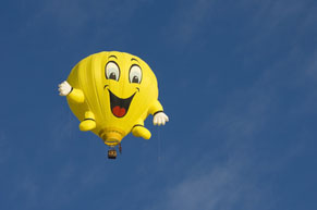Yellow balloon rising in the sky