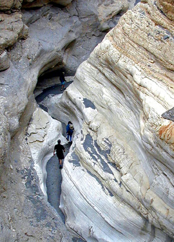 Hikers exploring the narrows of Mosiac Canyon, Death Valley National Park