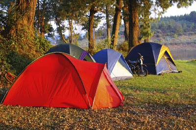 Four tents at a campsite by a river