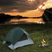 Green tent by camp fire with lake sunset in background