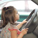 Little girl play driving in a car