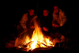 People sitting round a blazing campfire