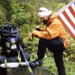 Hiker Scot Ward holds an American flag as he rests against a rock in the woods