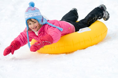 Little girl snow tubing