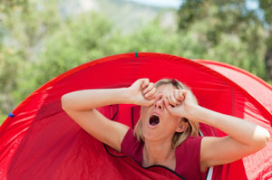 Lady waking up and yawning after sleeping in her red tent