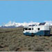 RV with Solar Panels on the roof near snow covered mountains