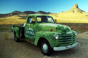 Old green truck parked on side of road with mountains in the background