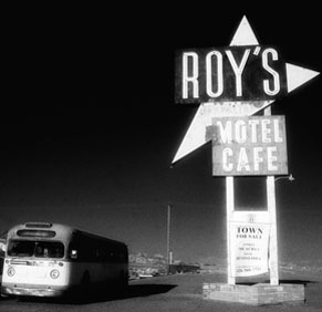 Bus parked next to Roy's motel café sign