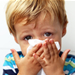 Young boy blowing his nose on a kleenex
