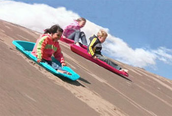 Kids sand sledding at Great Sand Dunes National Park