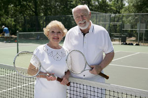 An elderly couple playing tennis