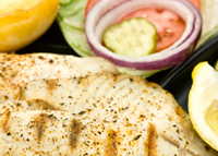 Grilled tilapia with salad and lemon