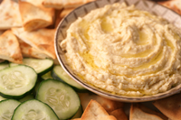 Bowl of hummus with cucumbers and pita bread