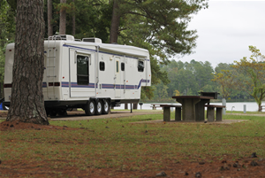 A trailer sits beside a lake at a campground