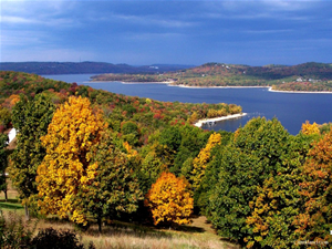 Yellow and green trees sit in the foreground with Table Rock Lake in the background