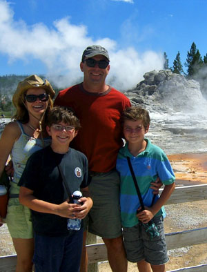 Bacon Family at Yellowstone National Park standing in front of a geyser