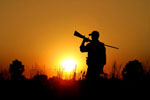 Hunter holding a rifle over his shoulder silhouetted by a setting sun