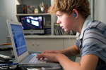 A teenage boy listens to music while using his laptop computer.