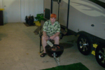 Steve Bowman sits in his garage, next to his trailer, grilling