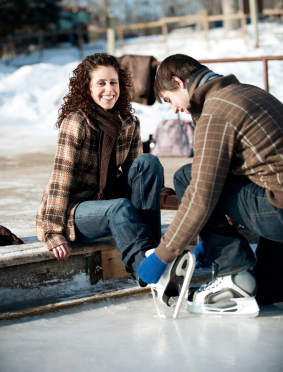 Young couple preparing to ice skate