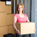 Young woman holding a box at a storage unit