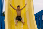 Young boy enjoying a ride on a water slide