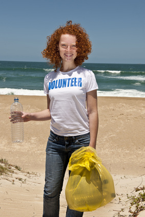 Lady collecting trash on the beach