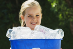 Little girl smiling and holding a blue recycling bin full of empty plastic bottles