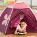 A young girl tent camping indoors