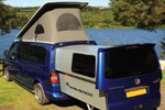 Blue VolksWagen Transporter DoubleBack Camper Van parked in field by lake
