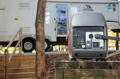 RV generator on a picnic table at campsite, in front of a Fifth Wheel