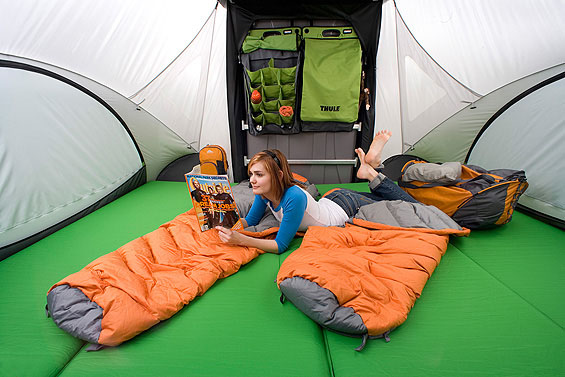 Interior view of the SylvanSport GO Camper Trailer in the big bed configuration with a lady lying and reading on the bed