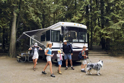 Family with their dog leaving their Class A motorhome parked at a campsite