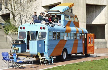Orange and blue RV bus parked with a group of people sitting on the roof