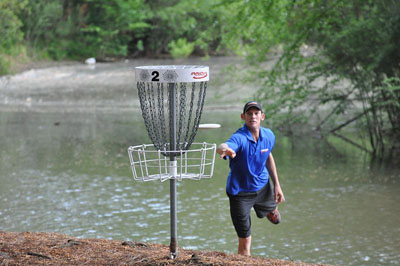 Disc golfer throws a frisbee at a basket with river behind him
