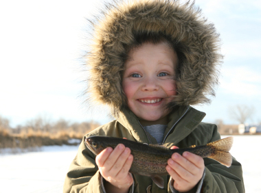 Child fishing in winter proudly displaying his catch
