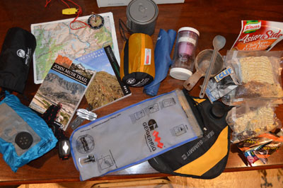 Hiking and camping gear spread across a table