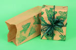 Brown paper bag being repurposed as Christmas gift wrap on green background
