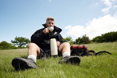 Hiker sitting in a grass field drinking from this thermos