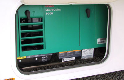 Green RV generator housed in RV compartment