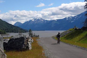 Cyclist on Indian to Girwood Bike Path with view of Turnagain Arm and mountains