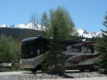 Motorcoach parked at RV site at Tiger Run RV Resort with the Rocky Mountains in the background