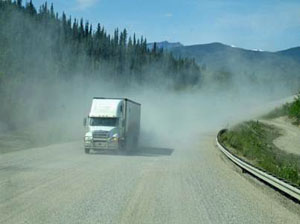 Rear view from RV showing dust kicked up on Alaskan Highway and truck driving behind