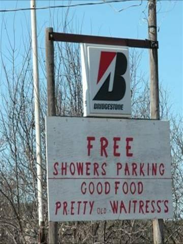 "Road sign that reads ""Free Showers Parking, Good Food, Pretty old waitress's"""