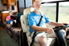 A man drives an RV while his wife sits on a couch behind and reads a book